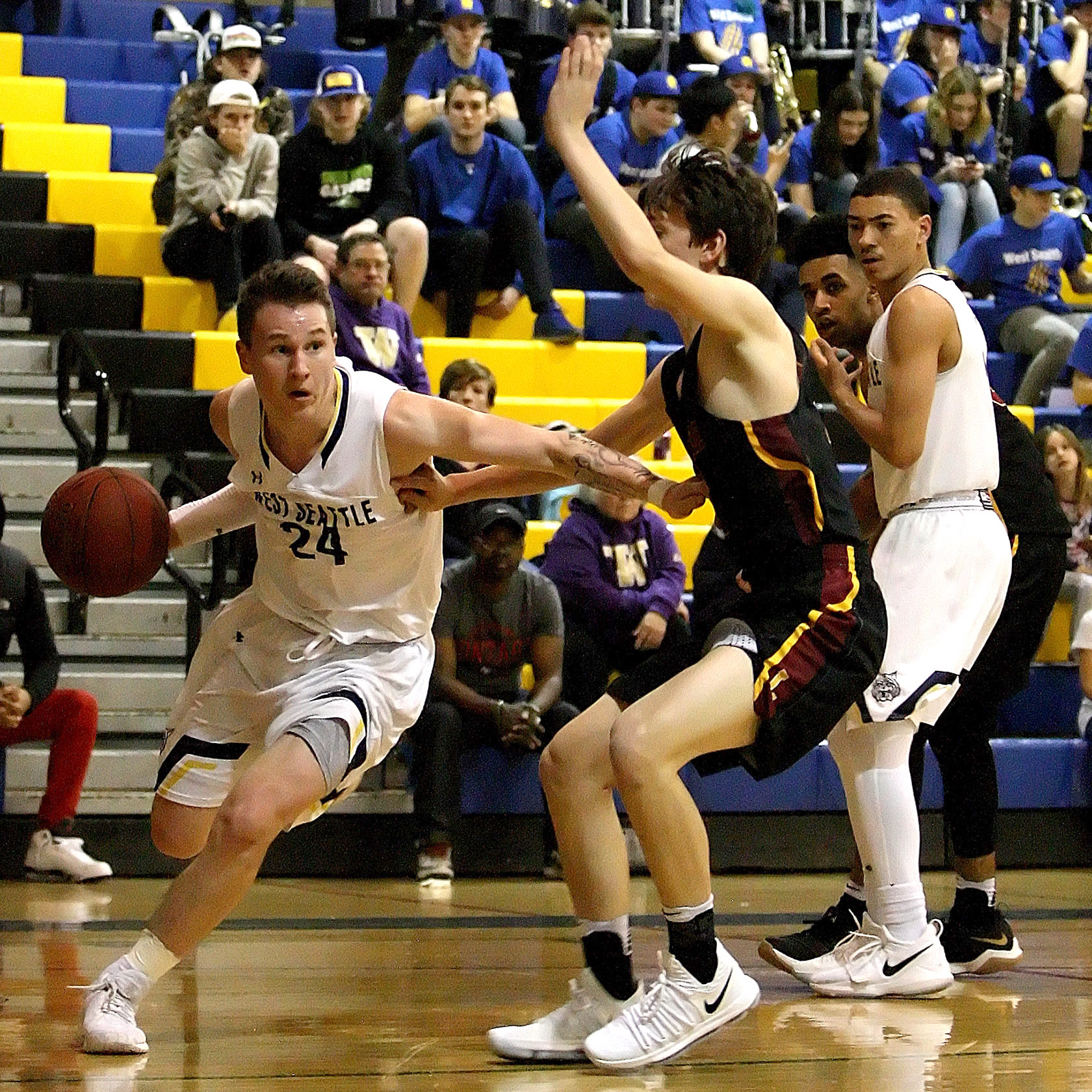 Simon Harris of West Seattle dribbles baseline against the defensive pressure of Lakeside's Robert Breyer.