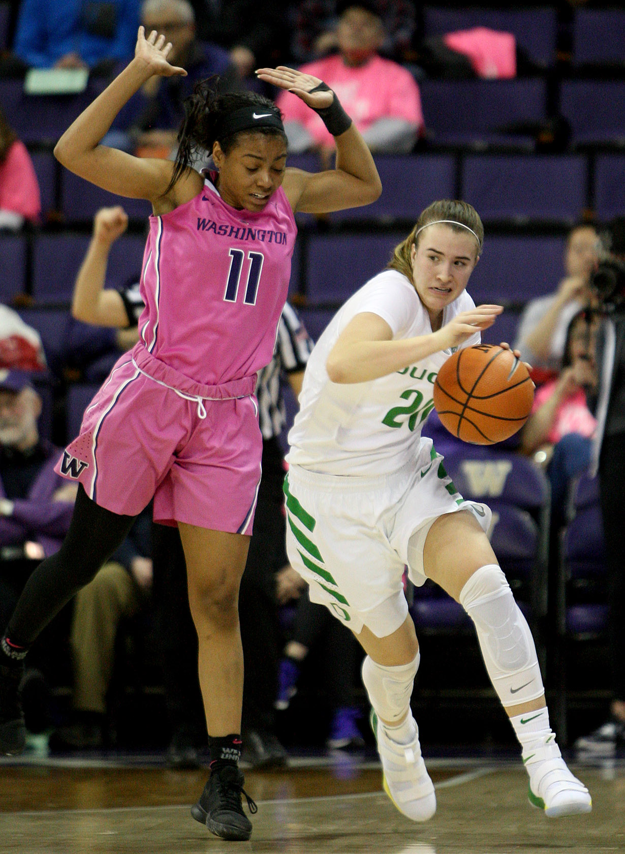 Sabrina lonescu of Oregon is fouled by Washington's Kierra Collier dribbling up court.
