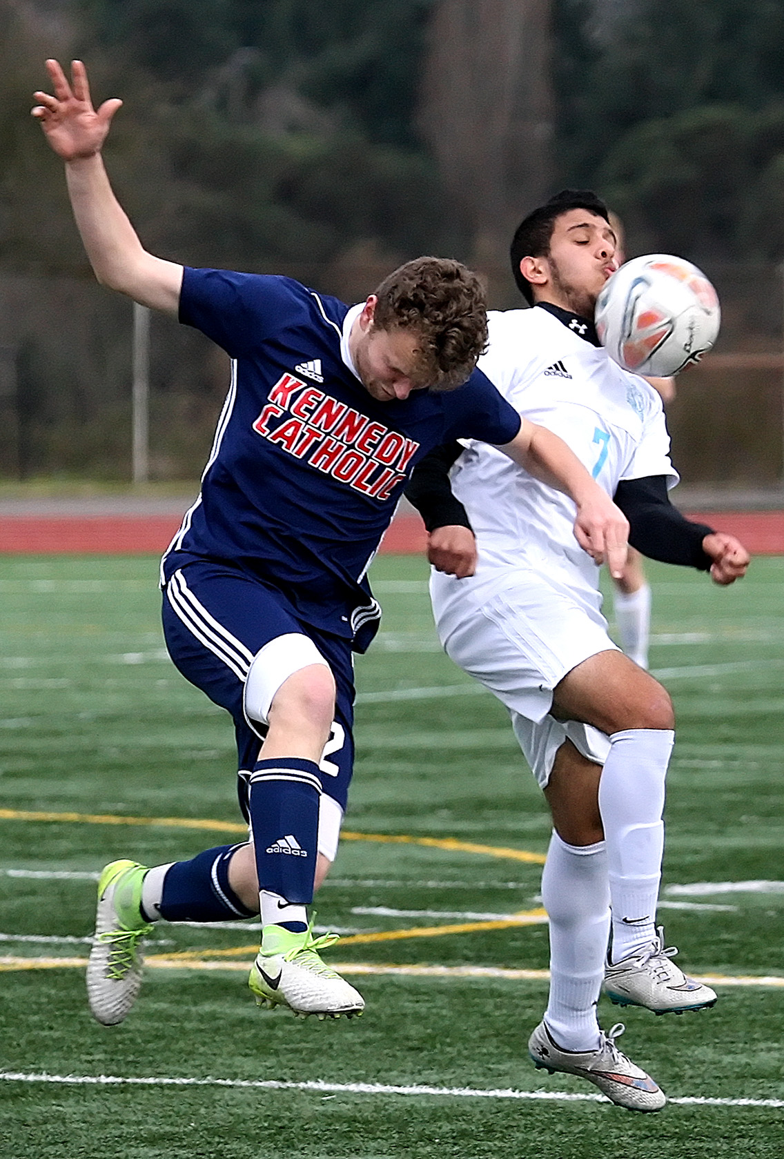Mustafa Alobaidi of Mt. Rainier chins the ball with pressure from Kennedy Catholic's Luke Tolton.
