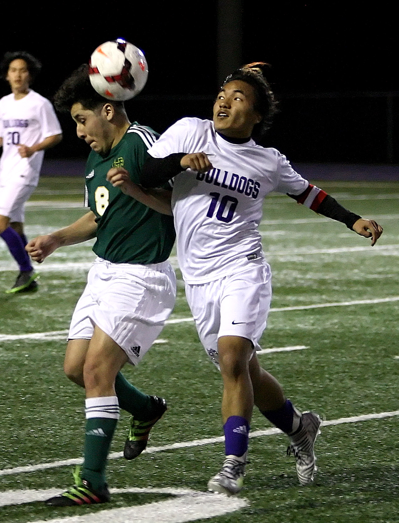 James Mung of Foster keeps his eye on the ball as he bumps into Foss 's Moses Ramos.
