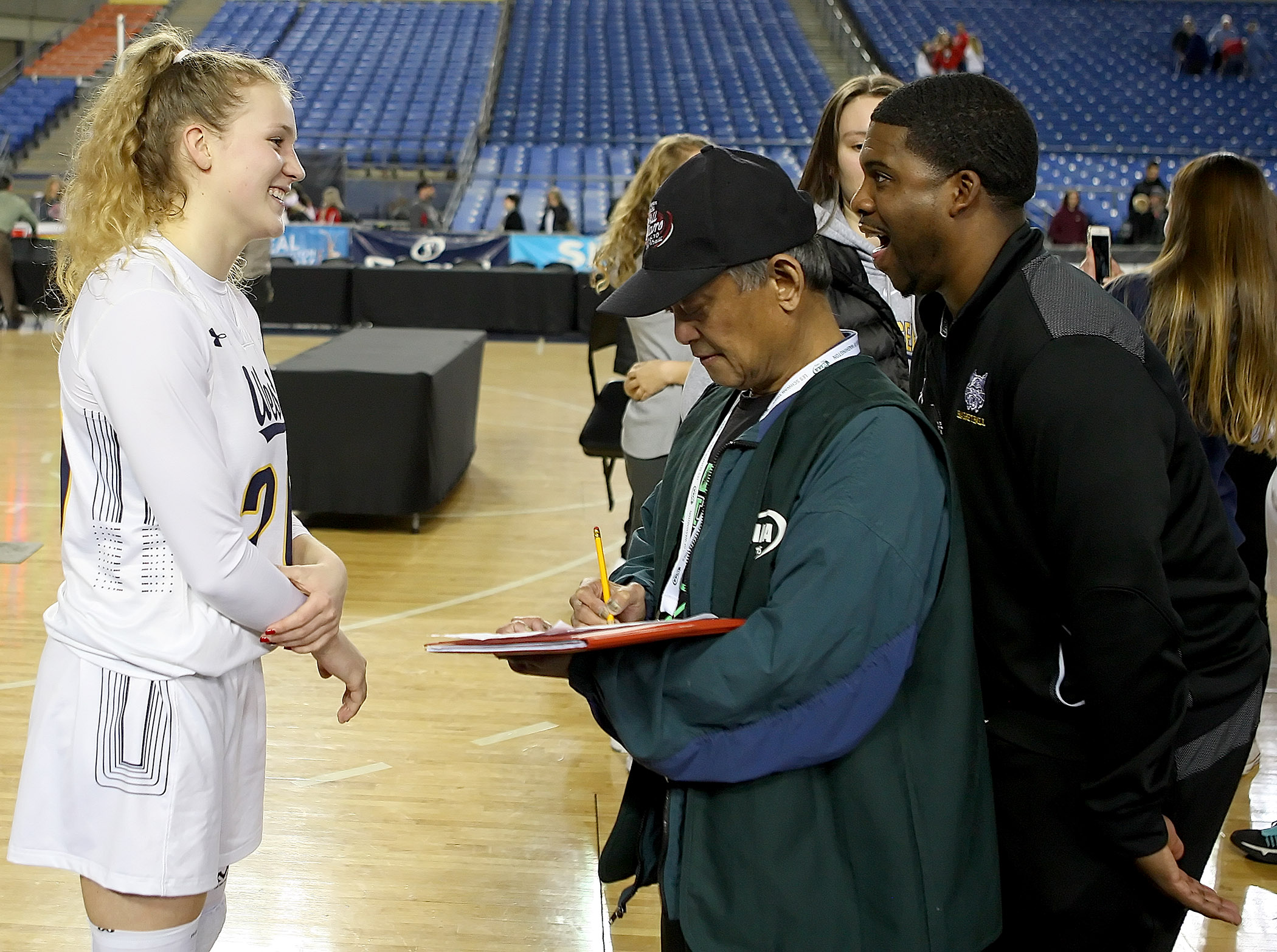 During an interview with West Seattle's Grace Sarver, coach Darnell Taylor jokingly harasses her, as he hides behind Westside Seattle's sports writer, Gerardo Bolong.