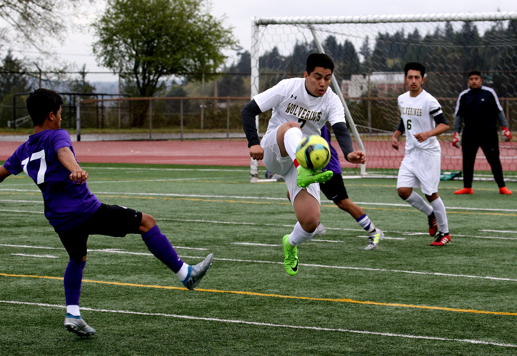 Josue Pedroza of Evergreen does a jump kick to get the ball away from the goal.