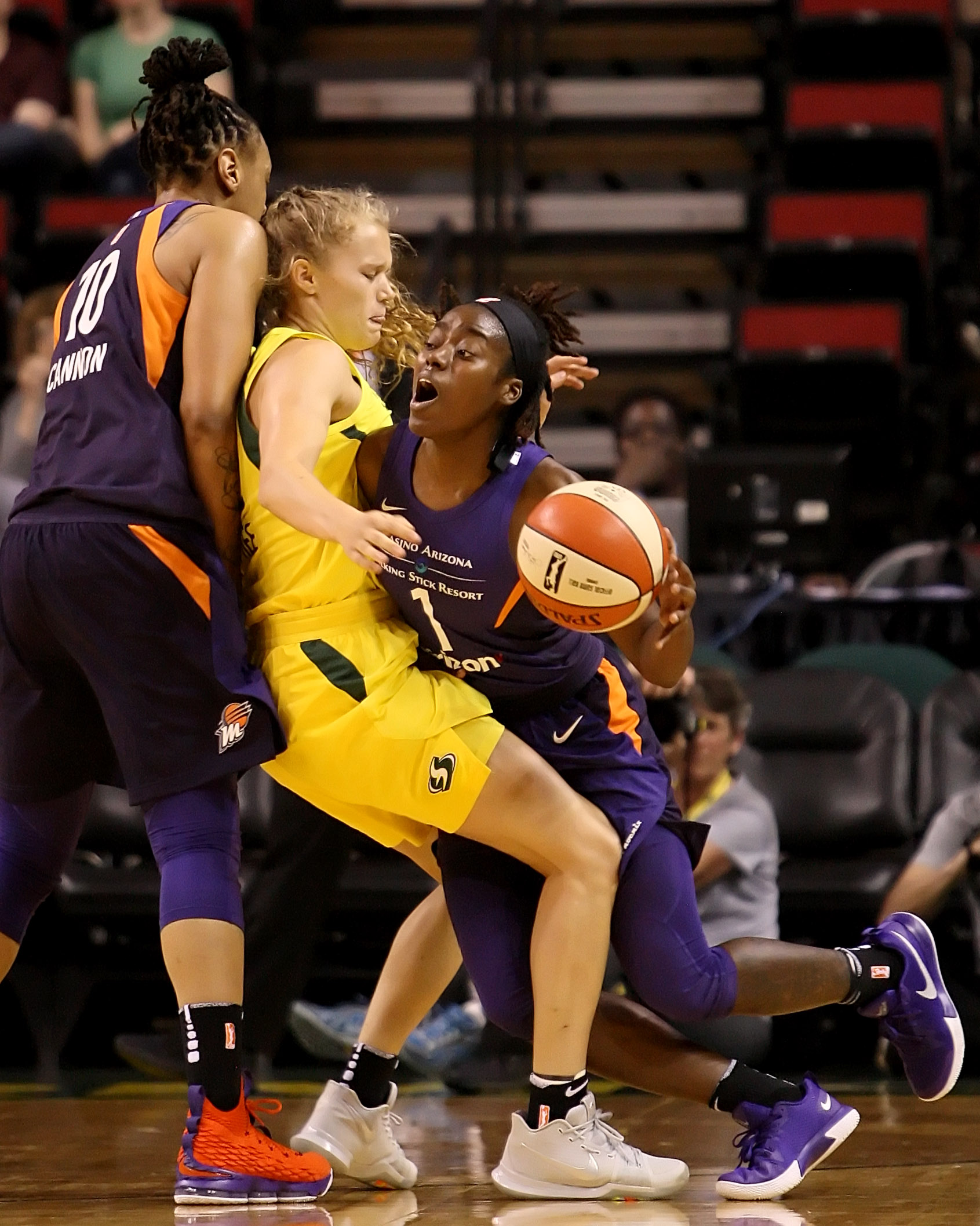 Brittany McPhee of the Storm gets sandwiched between Mercury players Emma Cannon and Imani Wright.