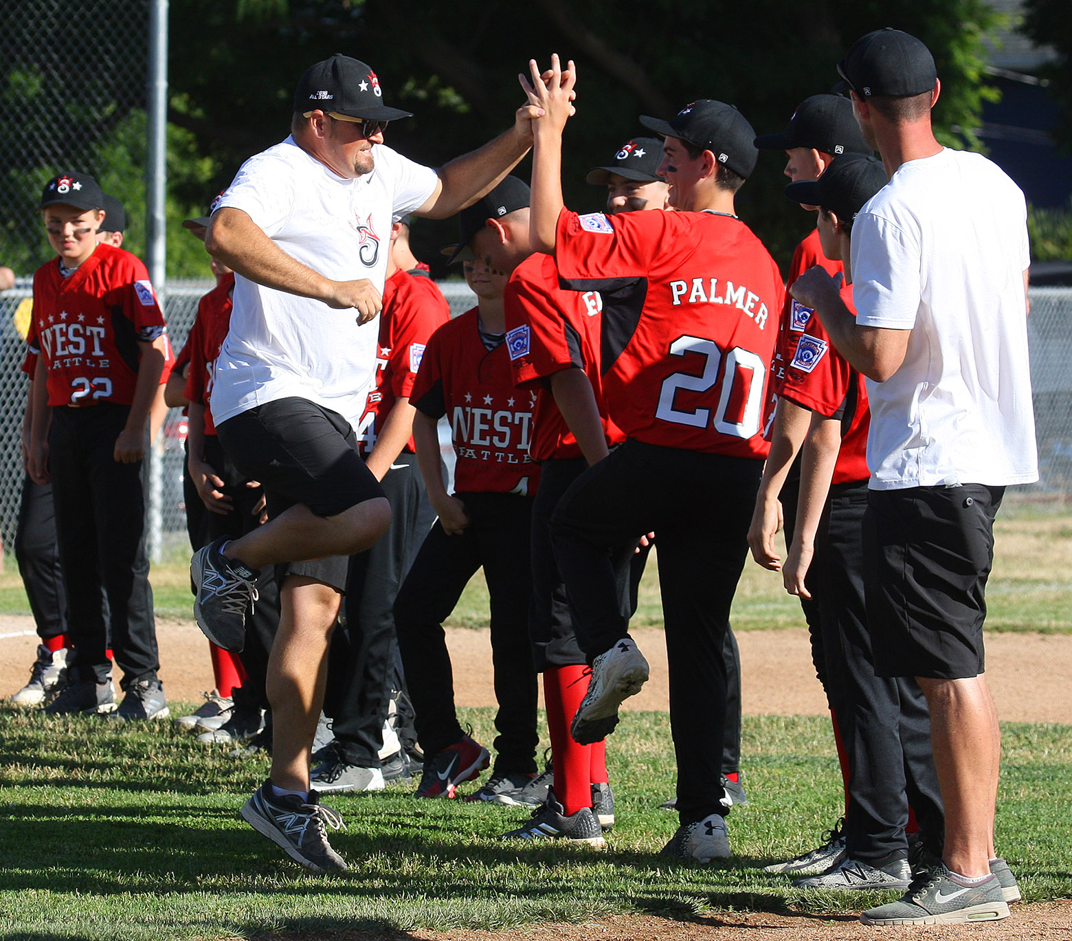 During team introductions a West Seattle coach gets in a high five and leaps for joy.