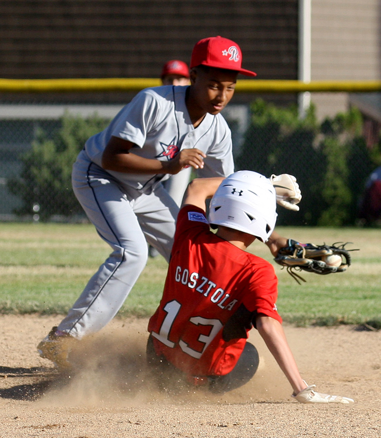 Miles Gosztola of West Seattle is safe sliding into second base as Renton's Marcus McCarthy attempts to tag him out.