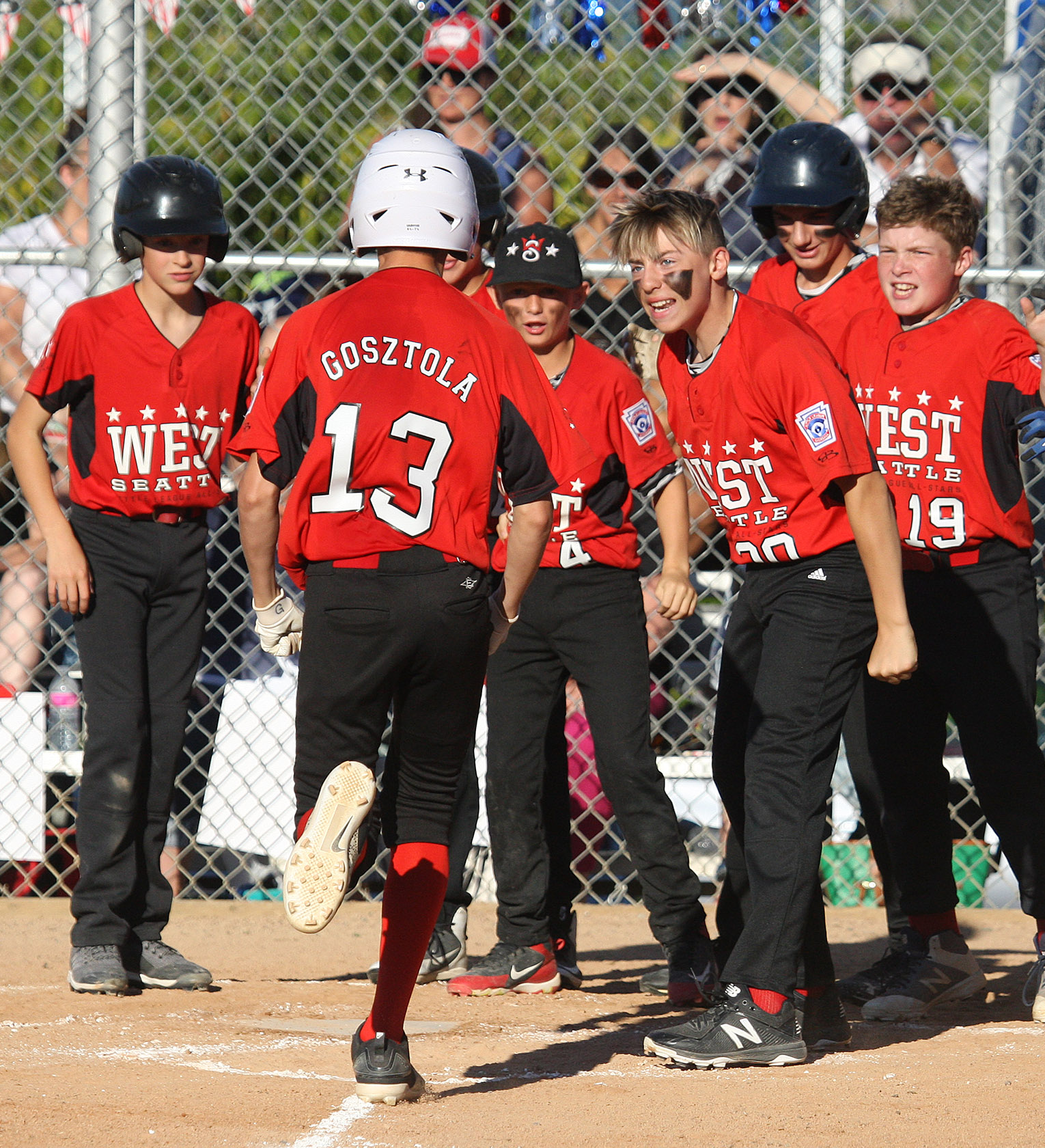 After hitting a home run Miles Gosztola of West Seattle is met by excited teammates at home plate.