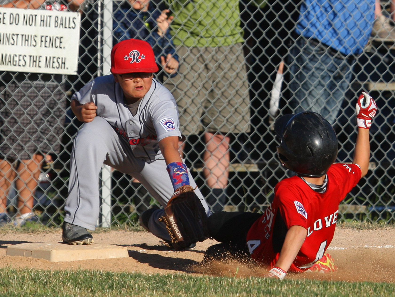 Wyatt Glover of West Seattle is tagged out by Renton's 3rd baseman Ethan Sugimoto attempting a triple.