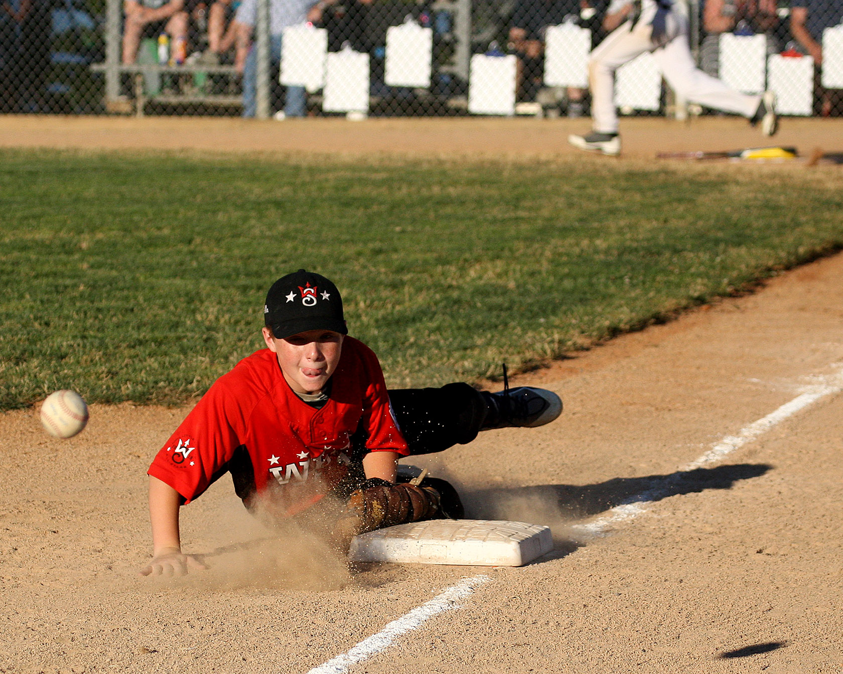 Third baseman Bobby Trigg of West Seattle can only watch as the ball gets by him and heads into left field.