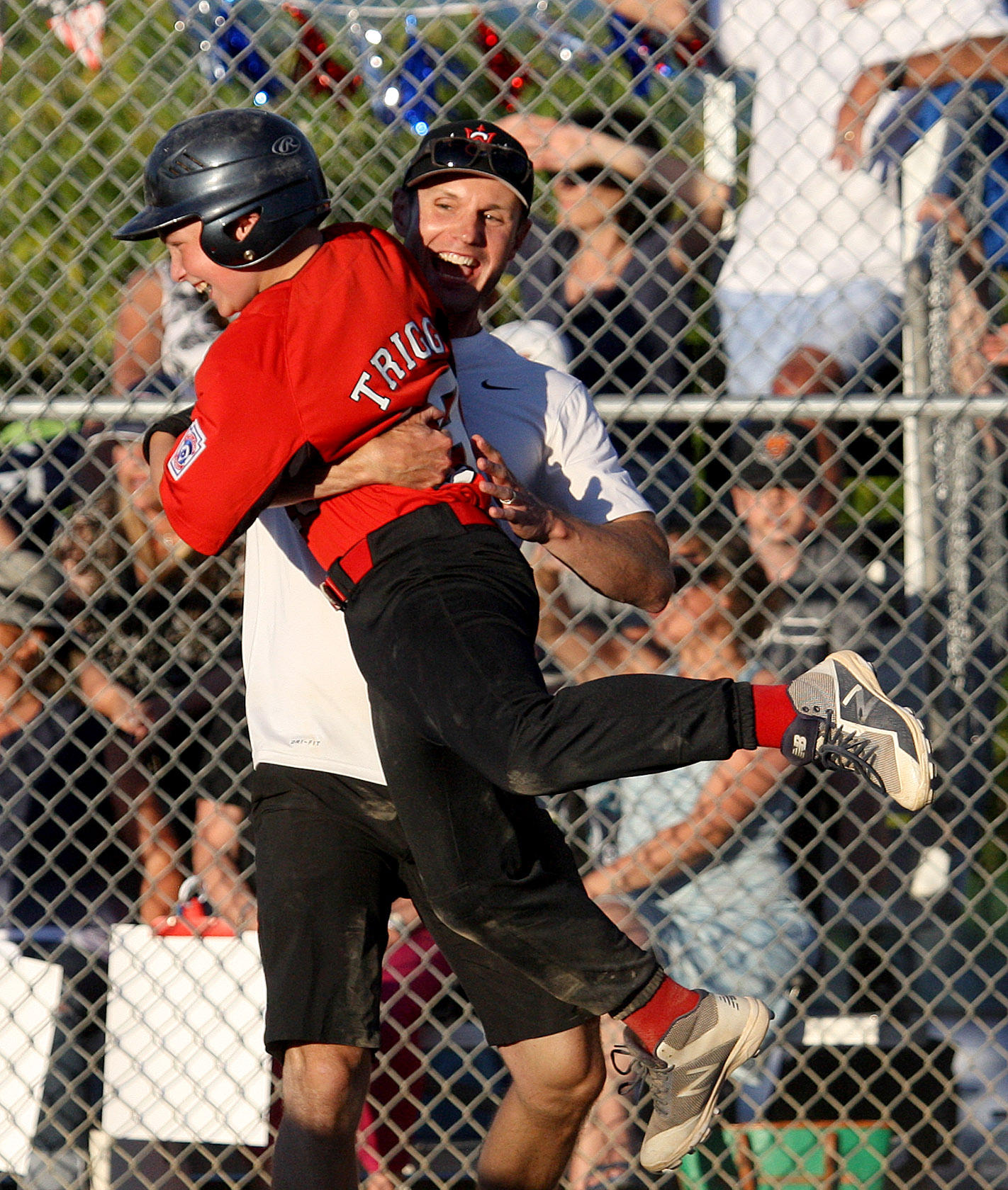 Bobby Trigg of West Seattle gets a lift from his coach after scoring the game winning run.